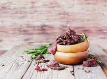 Viande lancée, vache, cerfs communs, bête sauvage ou biltong dans des cuvettes en bois sur une table rustique, foyer sélectif image libre de droits