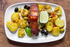 Viande saumonée cuite au four avec des pommes de terre et des légumes d'un plat blanc dans un restaurant Images stock