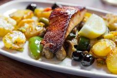 Viande saumonée cuite au four avec des pommes de terre et des légumes d'un plat blanc dans un restaurant Photos libres de droits