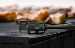 Viande sur le gril avec des pinces photos libres de droits