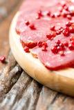 Viande traitée avec des grains de poivre sur la table en bois Images libres de droits