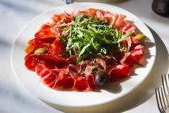 Viande, tranches minces du plat blanc avec le rucola et olives, garniture, photo fraîche et délicieuse de menu de nourriture Photos libres de droits