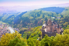 Vianden castle and valley in Luxembourg. Vianden castle and valley with river in Luxembourg through spring fresh leaves of the trees Royalty Free Stock Images