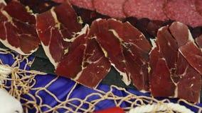 Viandes assorties d'épicerie, jambon, salami, lard sur un fond noir Fond de nourriture banque de vidéos