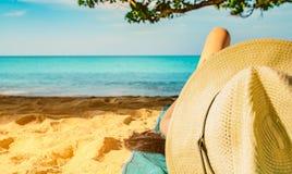 Η γυναίκα ξαπλώνει στην πράσινη πετσέτα που βάζει στην παραλία άμμου κάτω από το δέντρο και την ανάγνωση ένα βιβλίο Αργή ζωή στις στοκ εικόνα