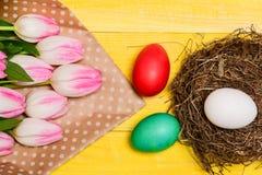 Vibrações da mola Ovos coloridos e flores frescas da tulipa do ramalhete na opinião superior do fundo amarelo A tradição comemora foto de stock