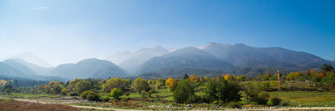 Vibrant autumn panorama background with colorful green, red,  yellow trees and mountains peaks Royalty Free Stock Images