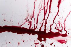Vibrant Blood Splat on White Bath Porcelain. Fresh red blood splat on white porcelain with specks from the impact. Copy space area for horror themed concepts and Stock Photography