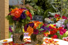 Vibrant Bouquets. Two vibrant bouquets of oranges and purples with evergreen against a spring garden setting stock images
