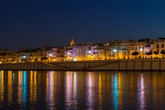 The vibrant Calle Betis in Seville. The vibrant calle Betis english translation: Betis Street in Sevilla during blue hour. The street is located in Triana and on stock photography