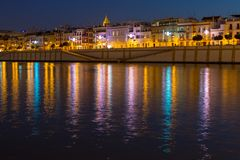 Calle Betis in Seville with reflections in the water. The vibrant calle Betis english translation: Betis Street in Sevilla during blue hour. The street is royalty free stock photography