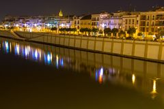 Calle Betis with reflections in the river. The vibrant calle Betis English translation: Betis Street in Seville during blue hour. The street is located in Triana royalty free stock image