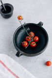 Vibrant Cherry Tomatoes on the Vine in Dark Clay Rustic Pot on Grey Kitchen Worktop Royalty Free Stock Image