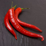 Vibrant Chillis. Three vibrant red chillis on a backdrop of dark slate Stock Photos