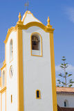 Vibrant church - Vertical. A vibrant church, white with yellow accents, set against a deep blue sky Stock Images