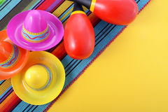 Vibrant Cinco de Mayo background. Vibrant Cinco de Mayo background with sombrero hats and maracas on bright festive background, with copy space Stock Images