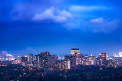 Vibrant city lit up at night beneath cloudy weather Stock Photography