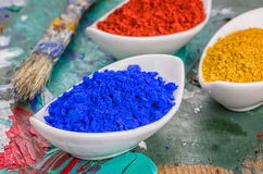 Vibrant color pigments in porcelain bowls on a wooden palette Stock Photography