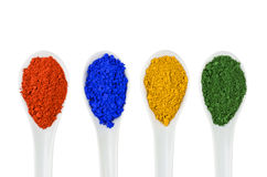 Vibrant color pigments in porcelain spoons Stock Photos