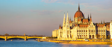 Vibrant color view of hungarian Parliament building, Danube and bridge at sunset, Hungary. Evening panorama of hungarian parliament building, Danube and bridge Royalty Free Stock Photos