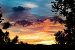 Vibrant Colorado Sunset. A vibrant, beautiful sunset in the Colorado front range, with a dark, contrasting forest in the foreground. A couple of lonely clouds stock image