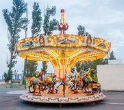 Vibrant colored carousel with lights and horses, close up, outdoor near beach, seaside Stock Photo