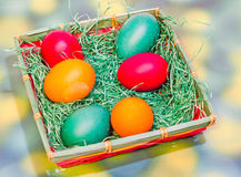 Vibrant colored easter eggs in a brown basket, gradient background, close up Stock Images