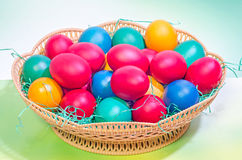 Vibrant colored easter eggs in a brown basket, gradient background, close up Stock Image