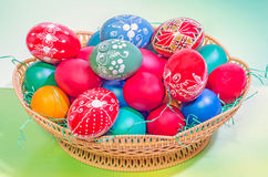 Vibrant colored easter eggs in a brown basket, gradient background, close up Stock Photo