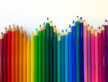 Vibrant colorful crafty background. Artistic mace of colored pencils arranged in a wave on white background Royalty Free Stock Images