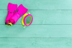 Vibrant colorful kids goggles and flippers. Arranged neatly in the corner on a pastel green stained wooden deck conceptual of a summer seaside holiday, overhead Stock Photos