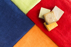 Vibrant colorful towels with organic soap Royalty Free Stock Photos