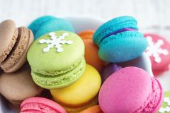 Vibrant colorfull macarons with christmas decoration on white wooden table royalty free stock images