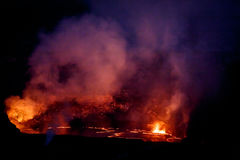 Vibrant colors, reds, pinks and yellows  surround crater of active volcano glowing in the nighttime sky Stock Photo