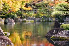 Vibrant colors and spectacular nature at Koko-en Gardens in Himeji. Spectacular nature and autumn colors reflected in the pond bordered by rocks covered in moss royalty free stock image