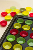 Vibrant cupcake wrappers (backing cups) inl  tray. Mini cupcake tin with vibrant colorful cupcake papers ready to be filled with batter Stock Photos