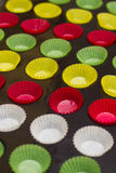 Vibrant cupcake wrappers (backing cups) in try. Mini cupcake tin with vibrant colorful cupcake papers ready to be filled with batter Royalty Free Stock Photo