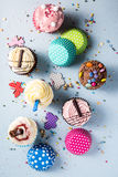 Vibrant cupcakes on blue background, party food concept Stock Photos