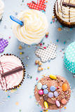 Vibrant cupcakes on blue background, party food concept Royalty Free Stock Photography