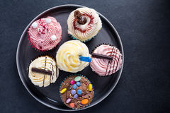 Vibrant cupcakes on plate on dark background Royalty Free Stock Images