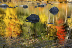 Vibrant fall colors in reflections on the Farmington River, Conn. Vibrant reflections of fall foliage on waters of the Farmington River in Canton, Connecticut royalty free stock images