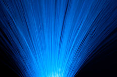 Vibrant fibre optics. Close up capturing many vibrant blue fibre optic light strands arranged over black Royalty Free Stock Photography