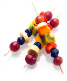 Vibrant fresh fruit kebabs for a healthy snack. With assorted grapes, strawberries, blueberries, banana, kiwifruit and orange on wooden skewers on white Stock Images