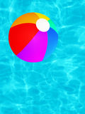 A Vibrant Fun Colored Floating Beach Ball. A colorful shaded fun water sports beach ball floating in a cool turquoise swimming pool Stock Image
