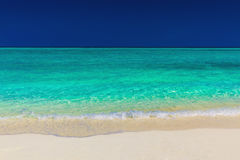 Vibrant green tropical sea, sand and blue sky Royalty Free Stock Image