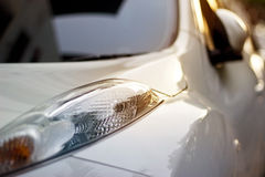 Vibrant headlights of white car in the sunset on street. Soft focus royalty free stock image