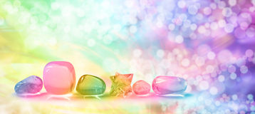 Vibrant healing crystals on Bokeh banner. Six rainbow quartz crystals in a row with vibrant rainbow bokeh background royalty free stock image