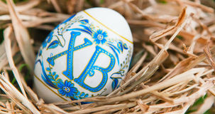 Vibrant holiday background with colorful Russian traditional Easter egg in dry grass nest Royalty Free Stock Photo