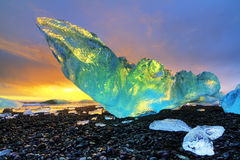 Vibrant iceberg Iceland. Very large and beautiful chunk of ice at the beach at Jokulsarlon, Iceland, at sunset in winter. HDR Stock Image