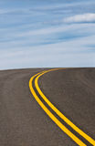 Vibrant image of highway and blue sky. With white clouds Royalty Free Stock Photography